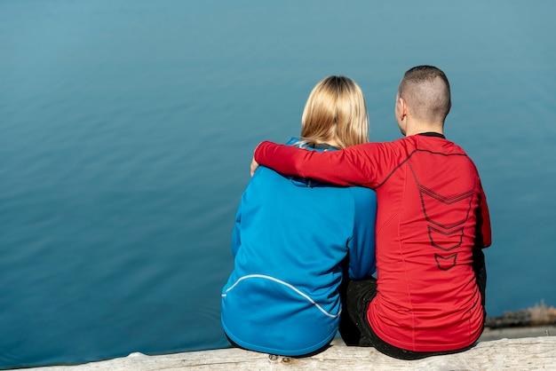 Achteraanzicht jong koppel knuffelen op de rand van het meer