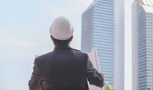 Achteraanzicht jonge adulte architect in een pak en witte bouwvakker staande met blauwe print.