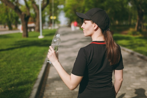 Achteraanzicht jonge atletische mooie brunette vrouw in zwart uniform en dop met fles, met water tijdens de training voordat ze buiten in het stadspark staat