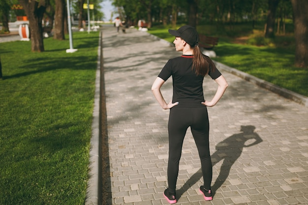 Achteraanzicht jonge atletische mooie brunette vrouw in zwart uniform, pet staand, rustend en opzij kijkend voor of na het hardlopen, training in stadspark buitenshuis