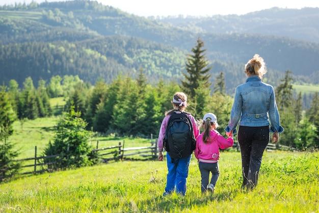 Achteraanzicht jonge moeder en twee dochters gaan de heuvel af die begroeid is met groen gras