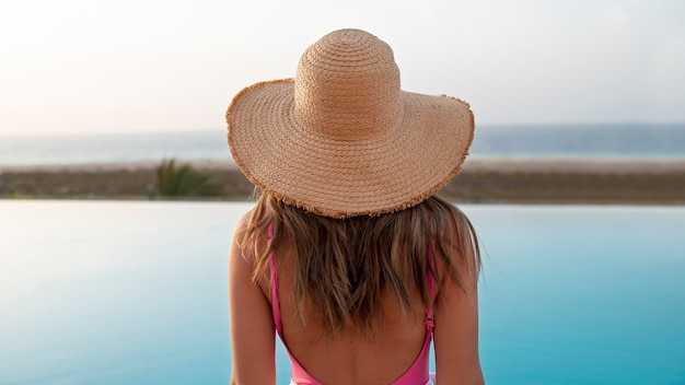 Achteraanzicht jonge vrouw die naar de oceaan kijkt
