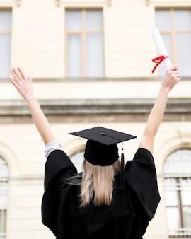 Achteraanzicht jonge vrouw viert haar afstuderen
