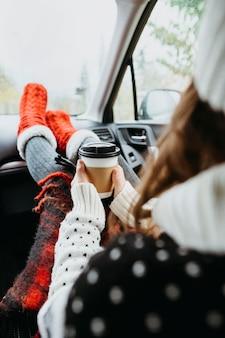 Achteraanzicht jonge vrouw zit in een auto met een kopje koffie