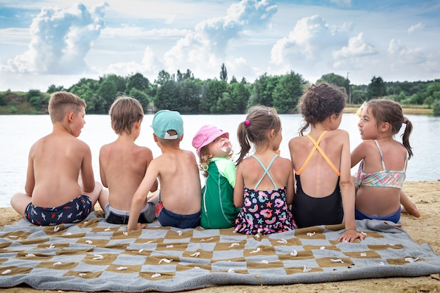 Achteraanzicht kinderen zitten bij de rivier en ontspannen na het zwemmen, zonnebaden, ijs eten.