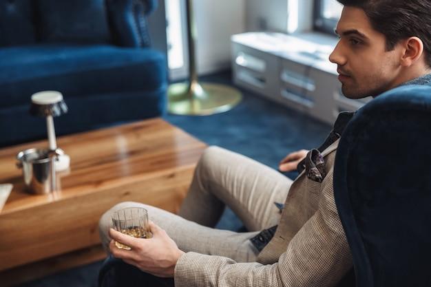 Achteraanzicht knappe jonge zakenman zittend in stoel binnenshuis in kantoor alcohol drinken.