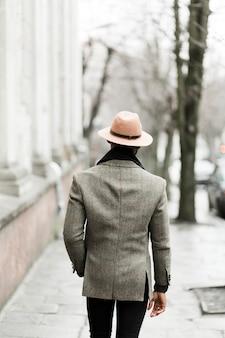 Achteraanzicht knappe man in grijze jas lopen