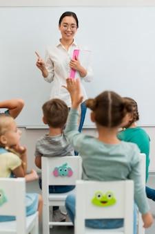 Achteraanzicht leerling die een vraag wil beantwoorden tijdens de les