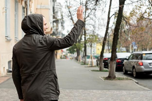Achteraanzicht man lopen op straat en groeten
