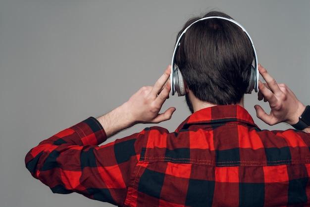 Achteraanzicht. man luisteren naar muziek met een koptelefoon