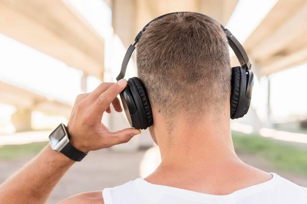 Achteraanzicht man luisteren naar muziek via de koptelefoon