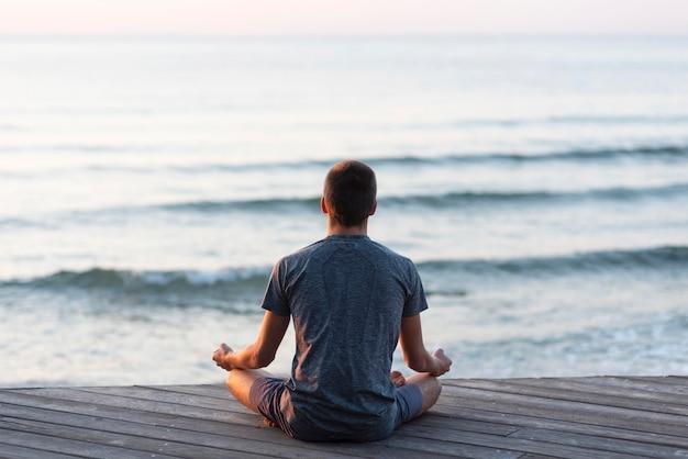 Achteraanzicht man mediteren op het strand