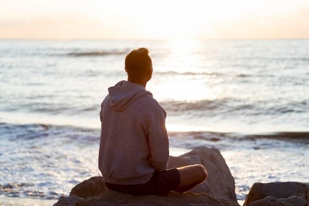 Achteraanzicht man ontspannen op het strand