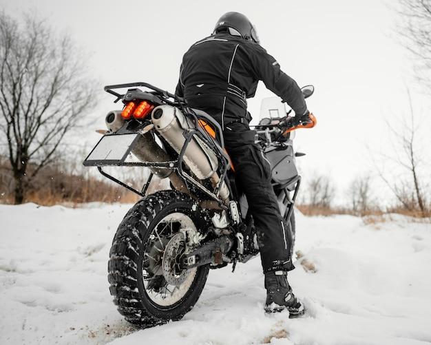 Achteraanzicht man rijden motorfiets op winterdag