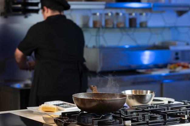 Achteraanzicht mannelijke chef-kok in de keuken koken