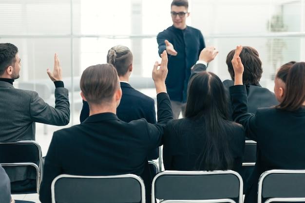 Achteraanzicht. medewerkers stellen vragen tijdens een zakelijke briefing