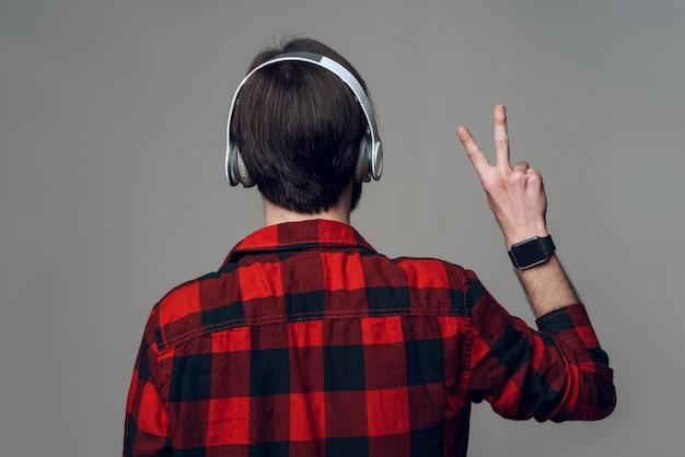 Achteraanzicht. mens die aan muziek met hoofdtelefoons luistert
