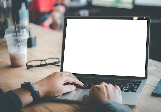 Achteraanzicht mockup-afbeelding van de hand van een vrouw die op een laptop werkt met een leeg wit bureaubladkopieerruimtescherm op een bureau