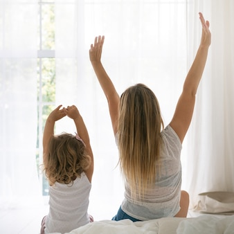 Achteraanzicht moeder en dochter die zich uitstrekt