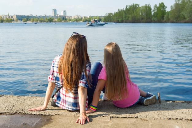 Achteraanzicht moeder en dochter kijken naar het water