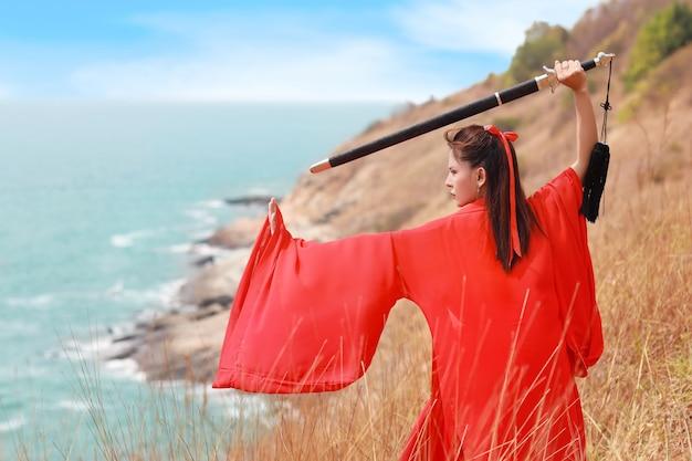 Achteraanzicht mooie aziatische vrouw in rood chinees kostuum met zwart zwaard