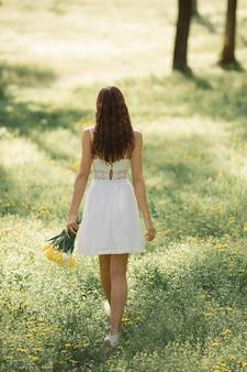 Achteraanzicht og aantrekkelijke vrouw in witte jurk met een boeket van lentebloemen die tegen lopen