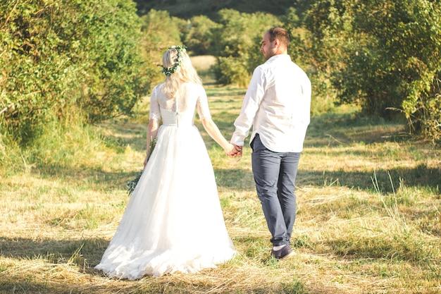 Achteraanzicht op bruid en bruidegom hand in hand op zonnige zomerdag outdoor bruiloft en relatie
