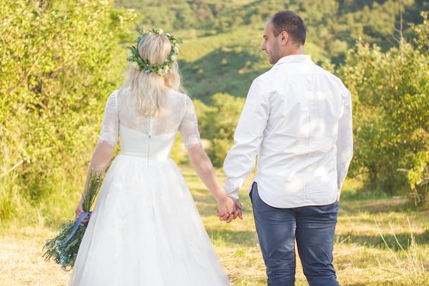 Achteraanzicht op bruid en bruidegom hand in hand op zonnige zomerdag outdoor bruiloft en relatieschap