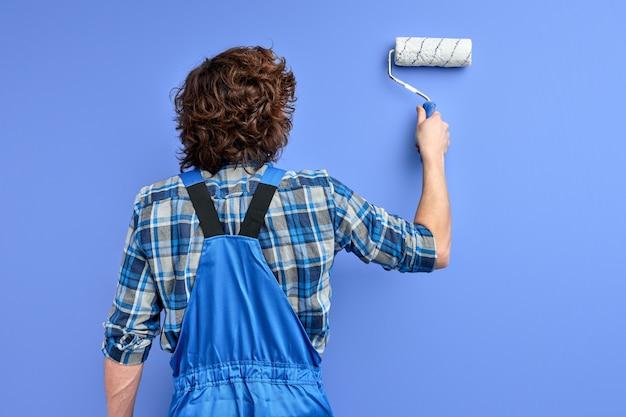Achteraanzicht op man in werkkleding muur repareren, met behulp van tekengereedschap.