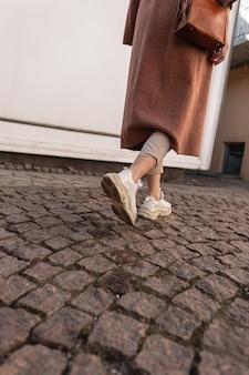 Achteraanzicht op moderne jonge vrouw in lange elegante jas in beige broek in lederen stijlvolle jeugdschoenen. modieus meisje in lente-casual kleding loopt langs de stenen weg in de stad. casual mode. close-up