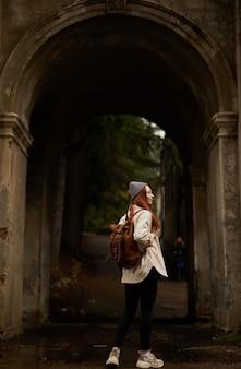 Achteraanzicht op reizigersvrouw met rugzak in historische oude boog die interessante oude...