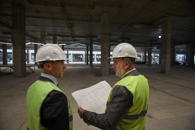 Achteraanzicht op twee zakenmensen die hardhats dragen en plannen vasthouden terwijl ze op de bouwplaats staan,