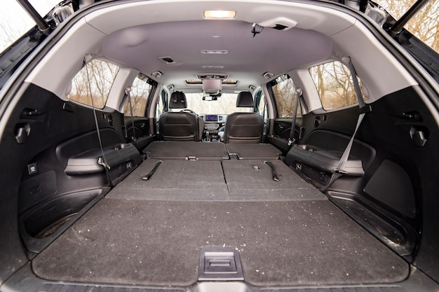 Achteraanzicht open kofferbak met neergeklapte passagiersstoelen. grote lege platte flor auto kofferbak close-up. enorme suv kofferbak