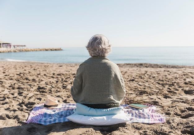Achteraanzicht oude vrouw op het strand