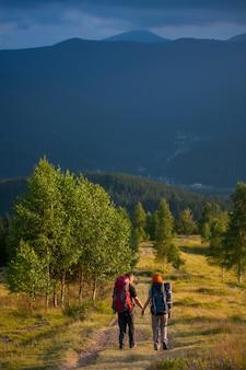 Achteraanzicht paar toeristen met rugzakken lopen langs een prachtig berggebied hand in hand
