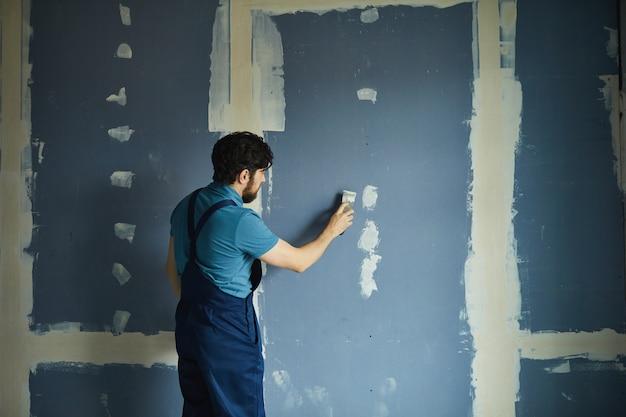 Achteraanzicht portret van bebaarde man aan het werk op droge muur tijdens het renoveren van huis, kopie ruimte