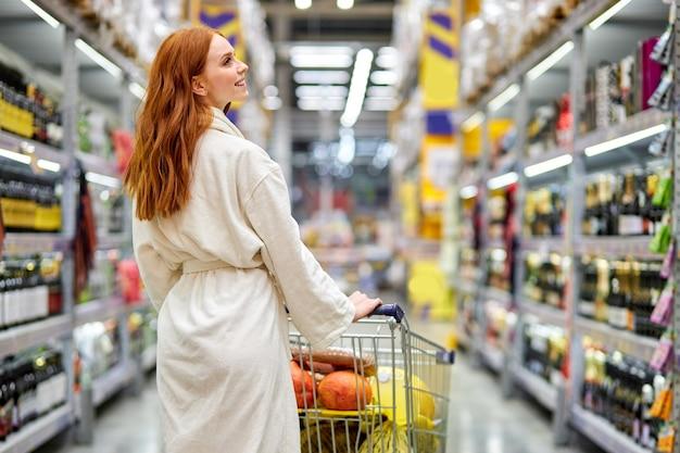 Achteraanzicht portret van de blanke vrouw met kar in de supermarkt, in de afdeling alcohol. geniet van winkelen
