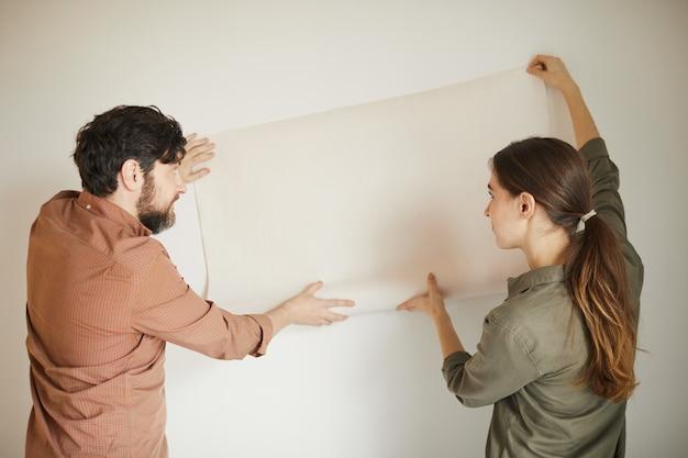 Achteraanzicht portret van echtpaar behang aan de muur houden tijdens het opknappen van huis, kopie ruimte