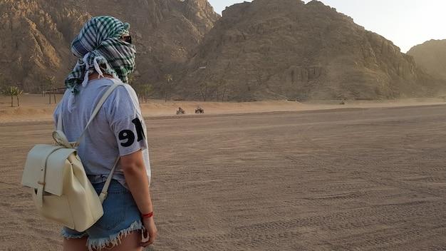 Achteraanzicht portret van een eenzame vrouw die kijkt naar een prachtige zonsondergang in de bergen in egypte. jong meisje in de woestijn. blanke vrouw in off-road woestijnsafari, westelijke woestijn.
