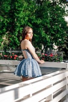 Achteraanzicht portret van een jonge chique vrouw in een blauwe feestelijke korte jurk staande op de open veranda...