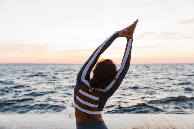 Achteraanzicht portret van een jonge vrouw die yoga-oefeningen doet