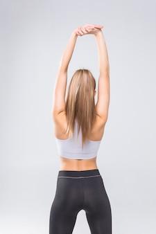 Achteraanzicht portret van een jonge vrouw die zich uitstrekt handen geïsoleerd