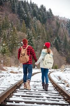 Achteraanzicht portret van een paar dat op het spoor loopt
