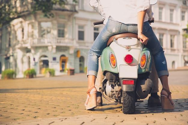 Achteraanzicht portret van een scooter met vrouwelijke benen