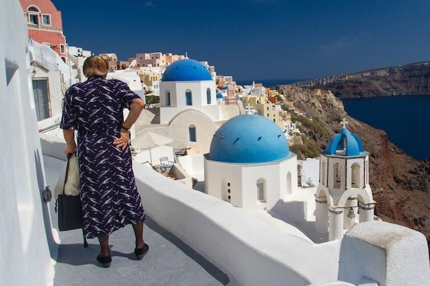 Achteraanzicht portret van eenzame onherkenbaar bejaarde vrouw kijken naar de stad