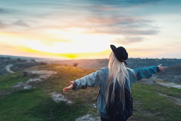 Achteraanzicht portret van jong gelukkig blond meisje met zwarte rugzak en pet, hand in hand als vliegtuig op de top van de heuvels bij zonsondergang. reis concept.