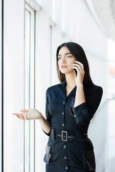 Achteraanzicht portret van jonge werknemer spreken met behulp van mobiele telefoon, kijkt uit het raam. vrouw met zakelijk gesprek, bezig op haar werkplek in de avond.