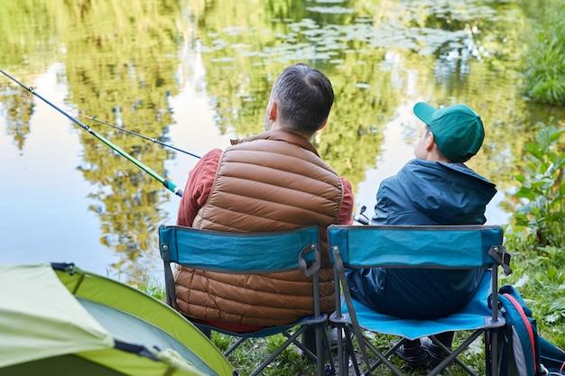 Achteraanzicht portret van liefdevolle vader en zoon samen vissen tijdens kamperen aan het meer, kopie ruimte