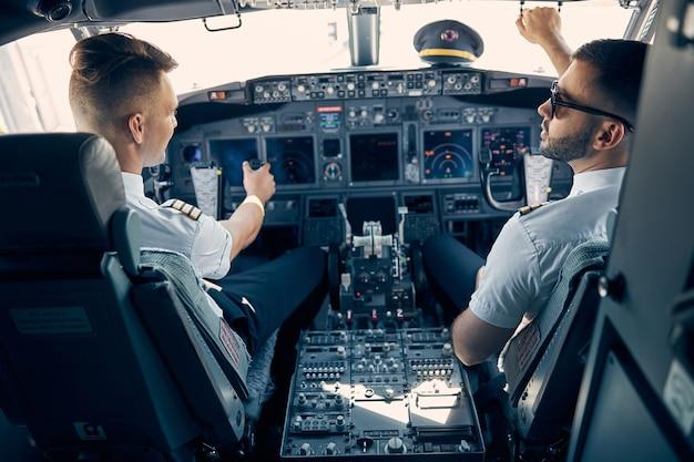 Achteraanzicht portret van professionele piloot aan het werk in het passagiersvliegtuig