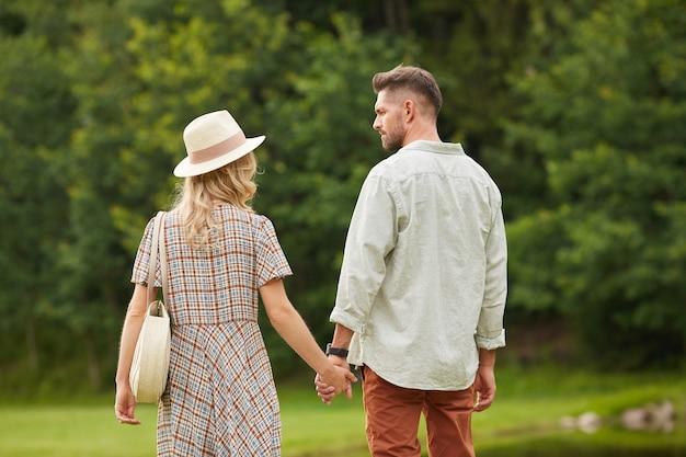 Achteraanzicht portret van romantische volwassen paar hand in hand tijdens het wandelen naar de rivier in een rustieke, landelijke omgeving